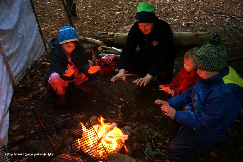 family-campfire-warming-hands-glow-dusk-autumn