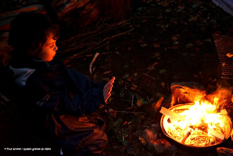 child-campfire-warming-hands-dark-glow