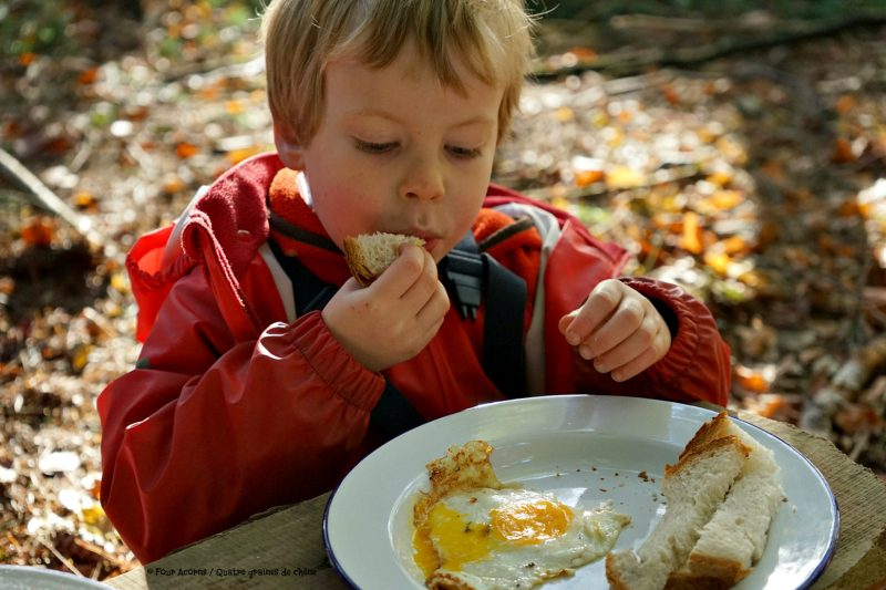 childd-eating-egg-outdoors-camping