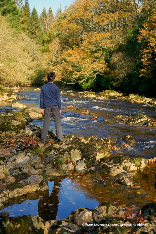 boy-standing-river-autumn-trees-reflection