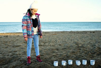 girl-standing-beach-beside-six-white-cups-sand