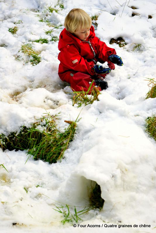child-red-playing-near-snow-tunnel
