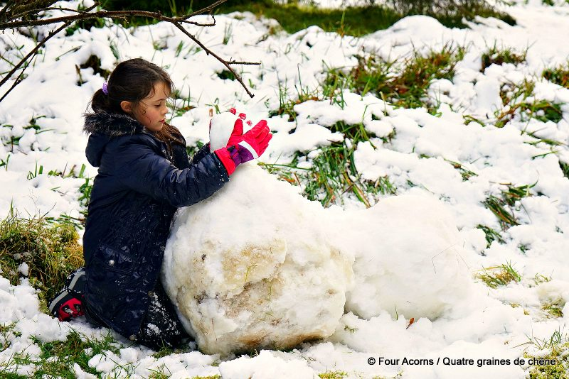 girl-playing-large-snowball-on-ground-snow