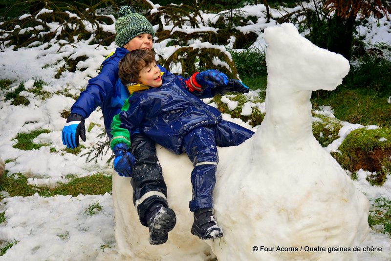 two-boys-playing-on-snow-horse-sculpture