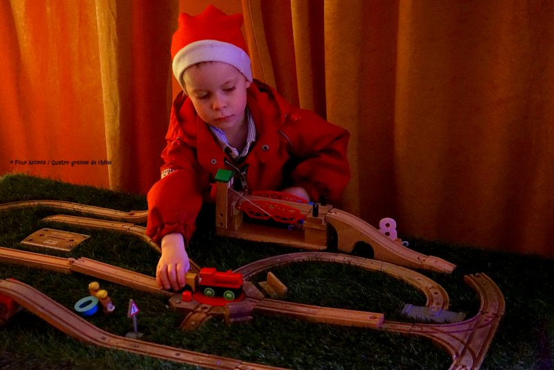 boy-red-suit-santa-hat-plays-toy-trains