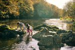 two-children- crossing-river-barefoot-autumn-sunshine