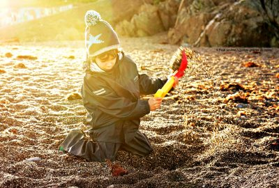 boy-raingear-bauble-hat-digging-beach-sunset-winter