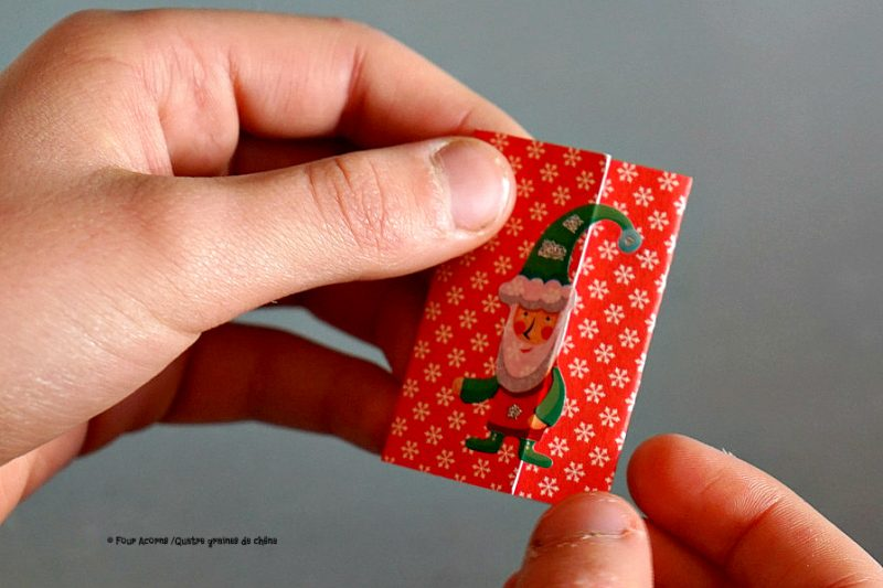 hands-holding-red-folded-note-with-elf-sticker