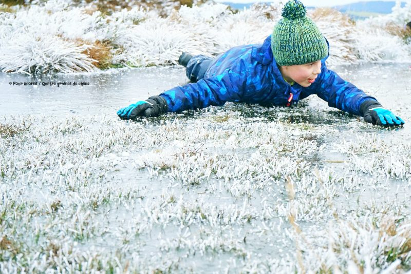 boy-in-blue-bauble-hat-lies-on-ice-arms-outstretched-wicklow-winter