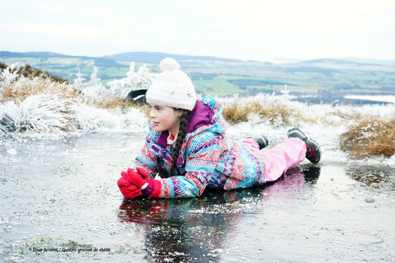 girl-bauble-hat-lies-down-on-ice-wicklow-winter