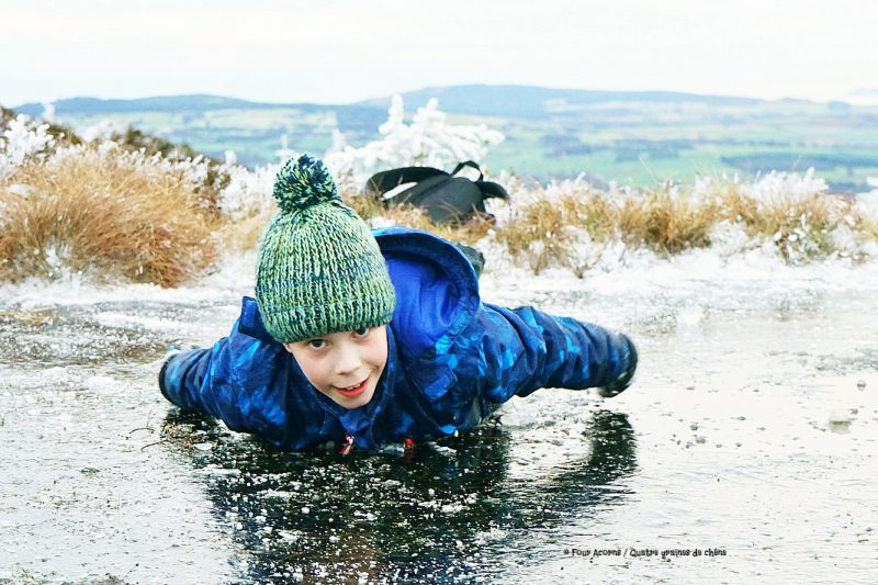 boy-bauble-hat-slides-on-belly-on-ice-face-forward-wicklow