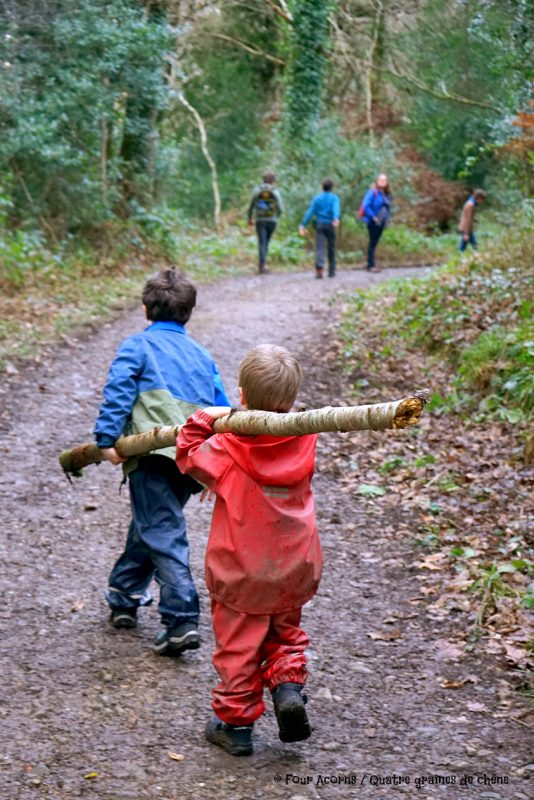 two-boys-puddlegear-walk-forest-carry-large-stick