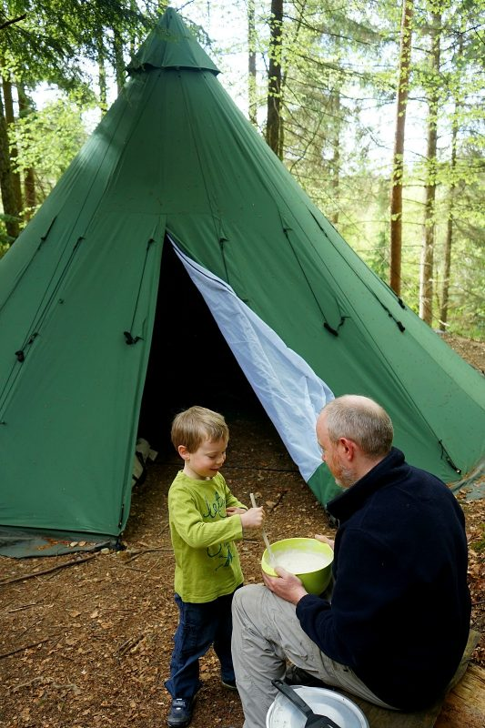 father-son-make-pancake-mix-outdoors-tipi