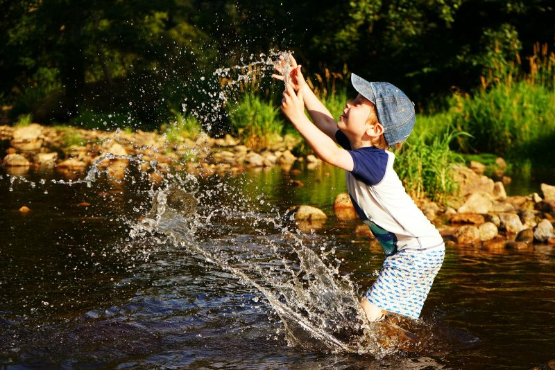 boy-splashing-river-sunshine-summer-heat