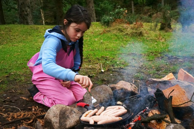 campfire-cooking-sausages-girl