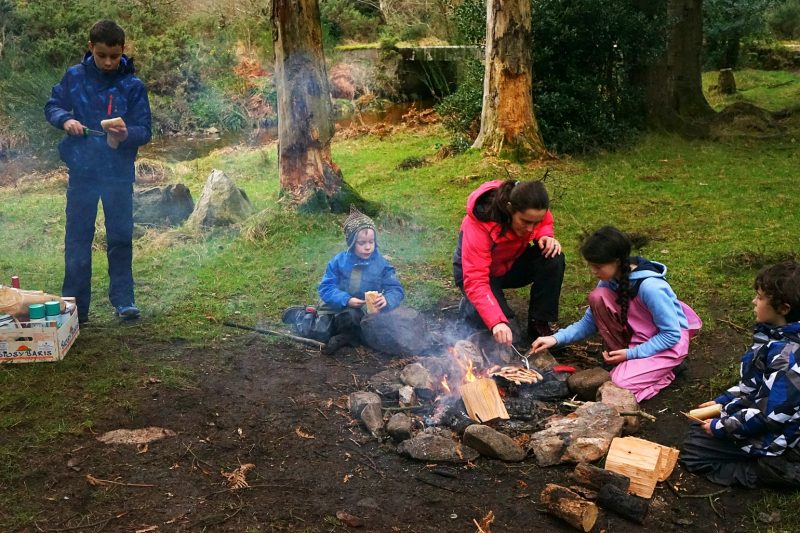 campfire-family-cooking-sausages-outdoors