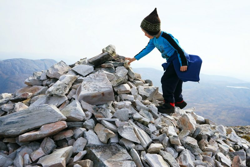 boy-adding-stone-to-cairn
